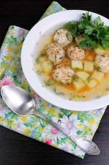Kippenbouillon van aardappelen, wortelen en gehaktballen bestrooid met dille