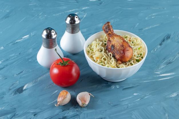 Kippenboutjes en noedels in een kom naast zout, tomaten en knoflook, op het marmeren oppervlak.