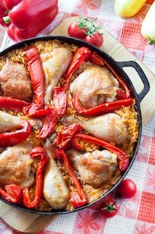 Kippendijen en benen gebakken boven een bedje van rijst en rode paprika