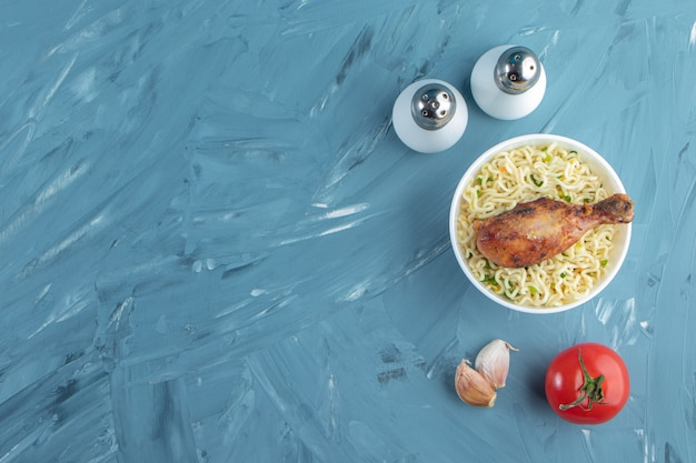 Kippendrumsticks en noedels in een kom naast zout, tomaten en knoflook, op de marmeren achtergrond.