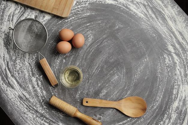 Kippenei, bloem, olijfolie, keukengereedschap op grijze tabelachtergrond.