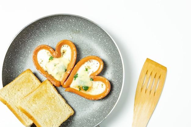 Kippenei in een worst in de vorm van een hart, in een pan met toast, geïsoleerd, bovenaanzicht