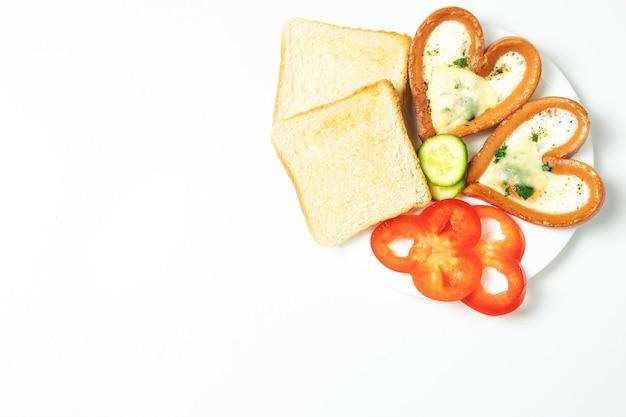 Kippenei in een worst, op toast, in een plaat, met rode paprika, geïsoleerd, bovenaanzicht