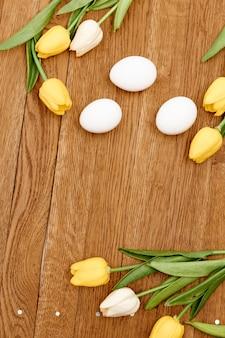 Kippeneieren boeket bloemen houten achtergrond vakantie pasen