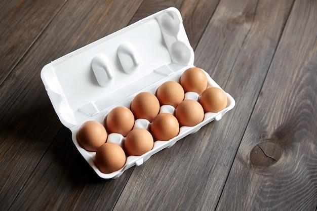 Kippeneieren in de lade op een bruin houten tafel