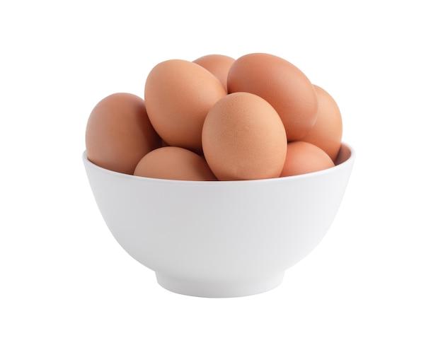 Kippeneieren in de witte geïsoleerde kom. rauw voedsel op het witte oppervlak met uitknippaden