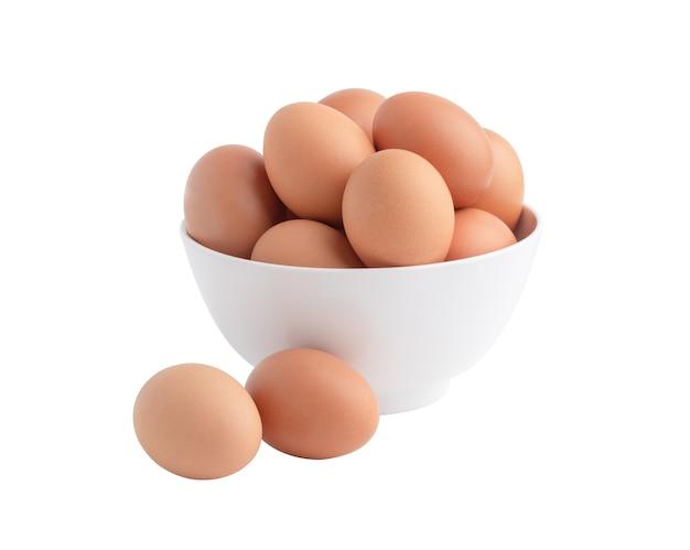 Kippeneieren in de witte kom en twee eieren op de vloer. rauw voedsel geïsoleerd op het witte oppervlak met uitknippaden