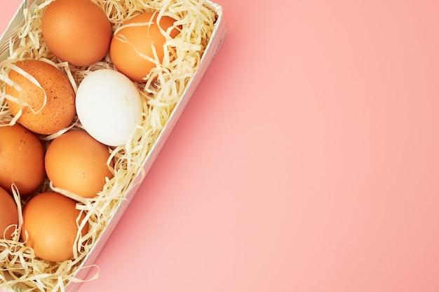 Kippeneieren in een doos op een roze pastelkleurachtergrond, exemplaren van de ruimte, flatlay