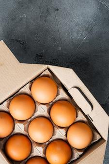 Kippeneieren in een eierdoos dienblad set, op grijze tafel, bovenaanzicht plat leggen, copyspace