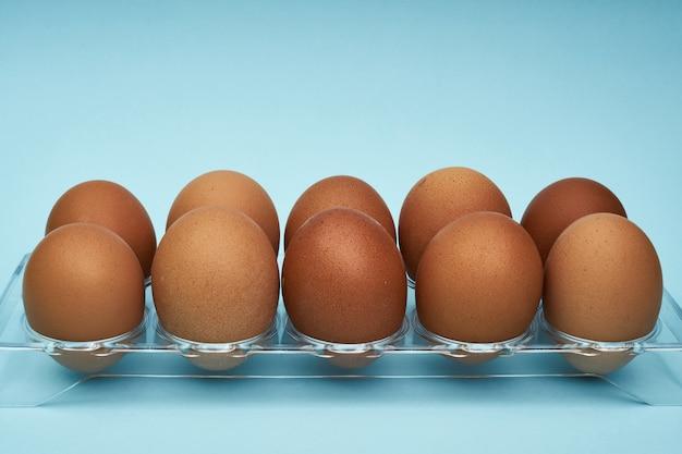 Kippeneieren in een eihouder. vol bakje eieren. een half ei, eigeel, schaal.