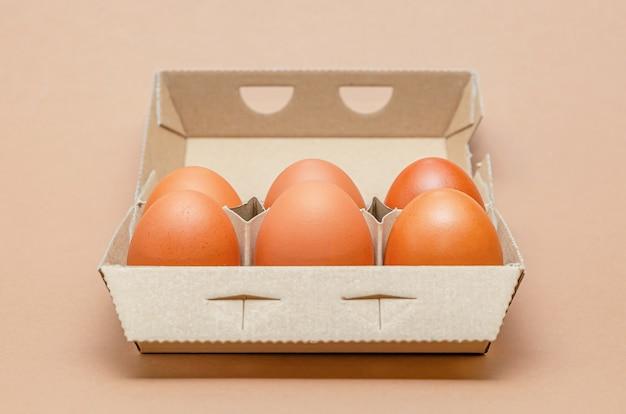 Kippeneieren in een kartonnen doos, ruimte voor tekst, groot formaat. bruine achtergrond.