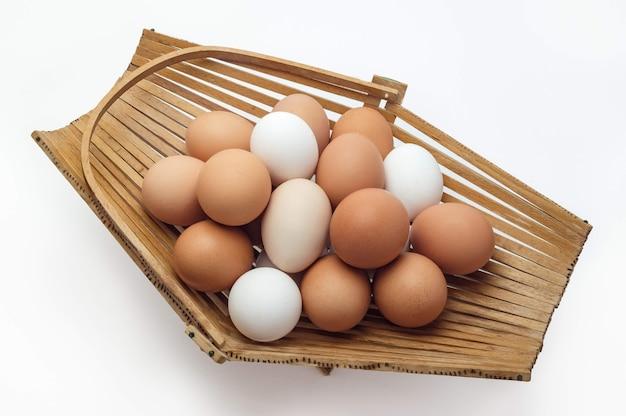 Kippeneieren in een mand met verschillende kleuren tinten op een witte achtergrond
