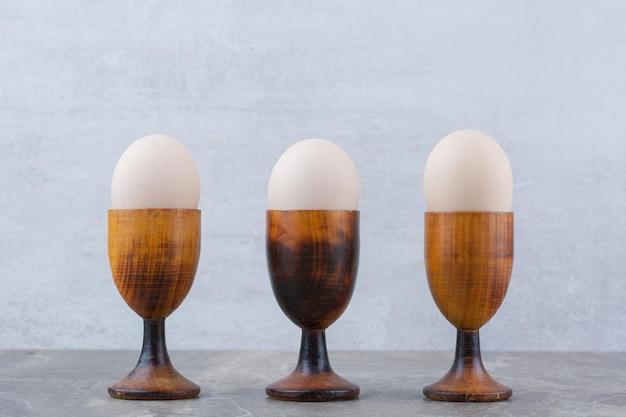 Kippeneieren in eierdopjes op marmeren achtergrond. hoge kwaliteit foto