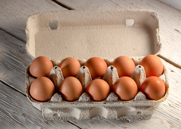Kippeneieren in kartonnen rek of ei vak op witte tafel
