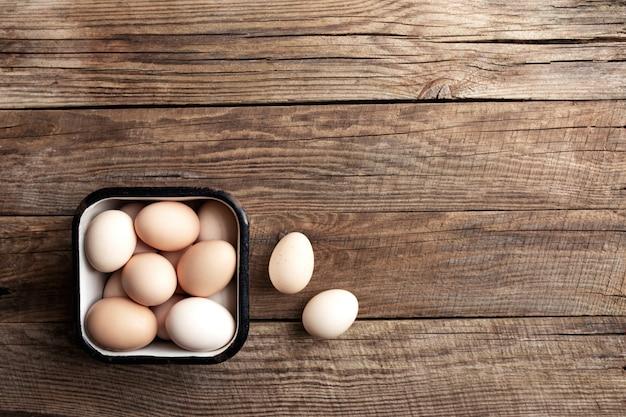 Kippeneieren in mand op houten organisch huishouden als achtergrond