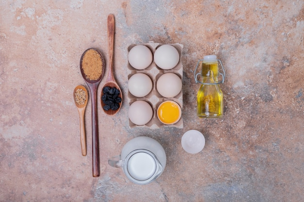 Kippeneieren, melk, olie en kruiden op marmeren oppervlak.