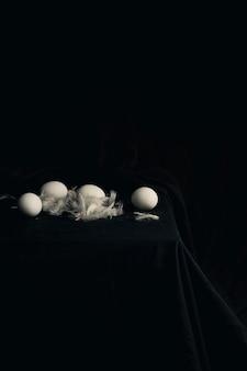 Kippeneieren met veren op de rand van de tafel tussen zwartheid