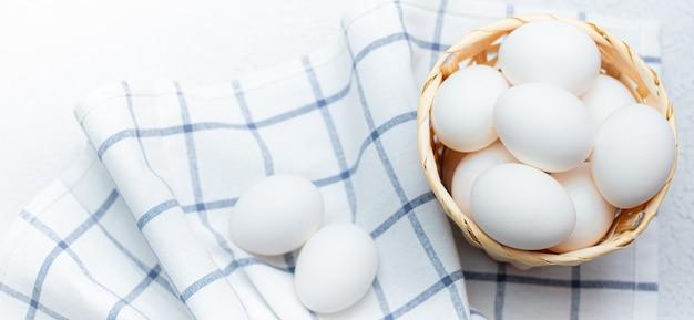 Kippeneieren op een gecontroleerde keukenhanddoek op een lichte tafel