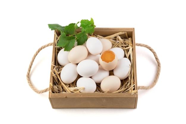 Kippeneieren van witte en bruine kleur met een gebroken ei in het midden.