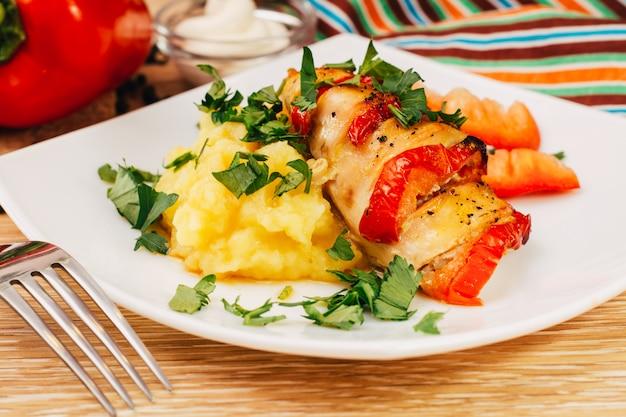 Kippenfilet gebakken met peper en aardappelpuree op een bord