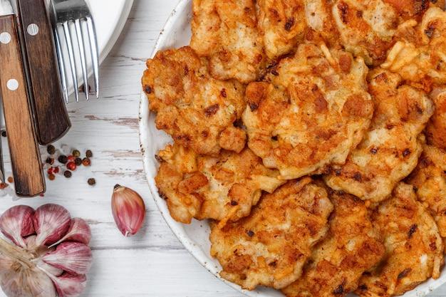 Kippenfritters op een plaat met tomaten en knoflook