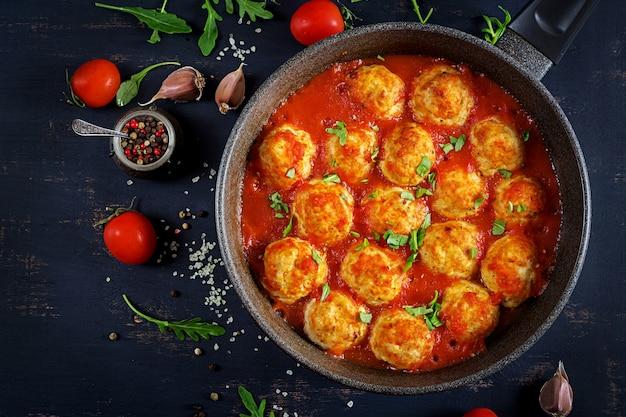 Kippengehaktballen met tomatensaus in een pan. diner. bovenaanzicht.