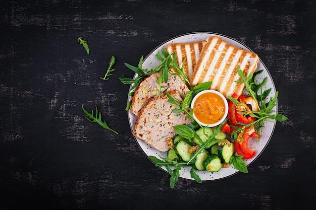 Kippengehaktbrood en verse salade en toosts. gezonde lunch of diner. bovenaanzicht, overhead