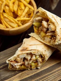Kippengehalte, shaurma binnen lavash met frieten op houten raad