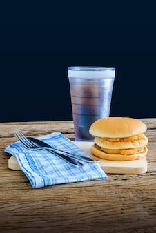 Kippenhamburger en glas kola op houten scherpe raad met mes en vork, servet