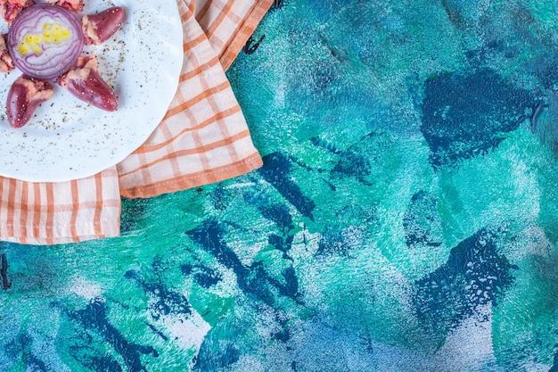 Kippenharten en ui in een bord op een theedoek snipperen
