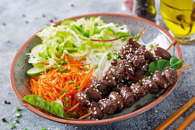 Kippenharten in pikante saus, noedels en groentesalade. gezond eten.