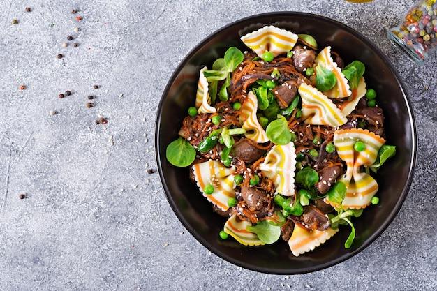 Kippenharten met wortelen in zoetzure saus met farfalledeegwaren. gezonde salade. bovenaanzicht plat leggen.