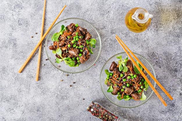 Kippenharten met wortelen, uien en groene erwten in aziatische stijl. bovenaanzicht