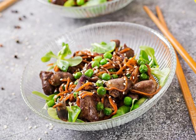 Kippenharten met wortelen, uien en groene erwten in aziatische stijl.