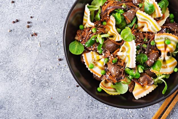 Kippenharten met worteltjes in zoetzure saus met farfalledeegwaren. gezonde salade. bovenaanzicht plat leggen.