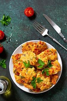 Kippenkoteletten gemaakt van gehakt met paprika, tomaten en greens bovenaanzicht