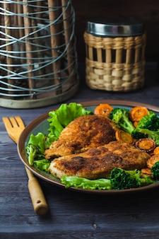 Kippenlapje vlees in broodkruimels met groenten op een plaat