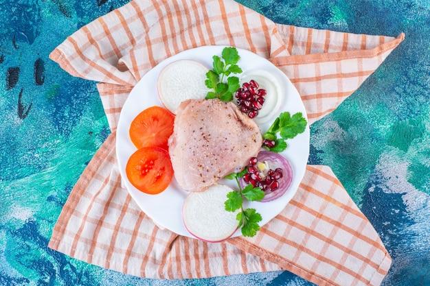 Kippenlever, slablaadjes en kippendrumstick op een bord op de theedoek