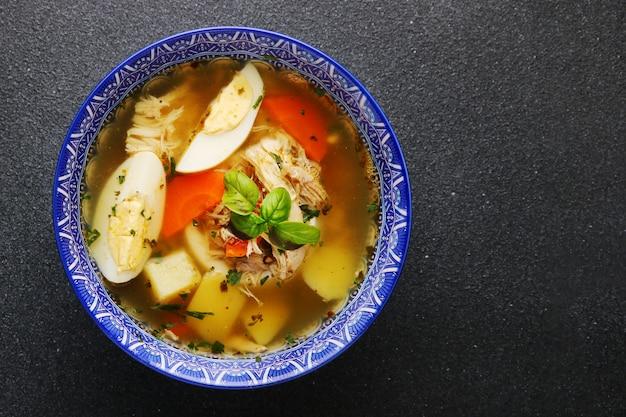 Kippennoedelsoep met ei, groenten en kippenvlees op donkere tafelbladweergave
