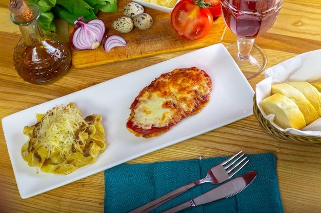 Kippenparmigiana en spaghetti dichte omhooggaand op een plaat op de lijst.