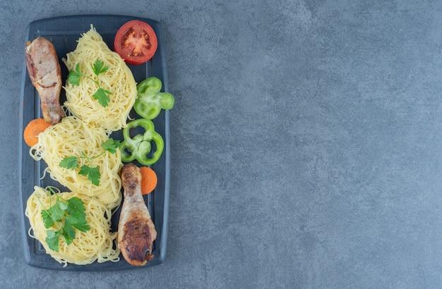 Kippenpoten en spaghetti op een houten bord.