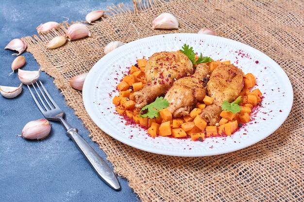 Kippenpoten gebakken en geserveerd met groenten.