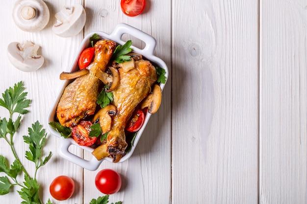 Kippenpoten gebakken met champignons en tomaten.