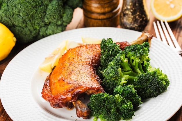 Kippenpoten met groenten op houten lijst.