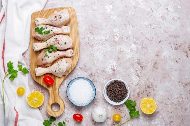 Kippenpoten met kruiden en zout klaar voor het koken op snijplank.