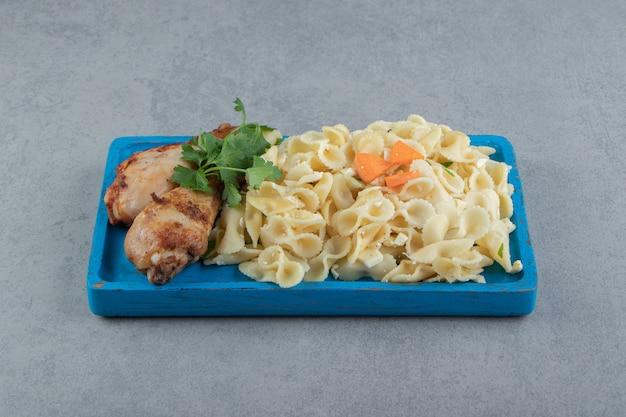 Kippenpoten met smakelijke pasta op blauw bord.