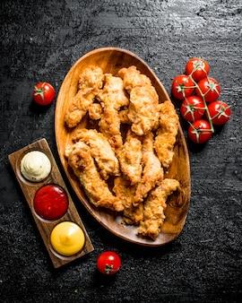 Kippenreepjes met sauzen en tomaten op tak op zwarte rustieke lijst