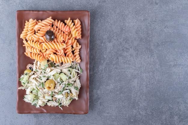Kippensalade en fusilli pasta op bruine plaat.