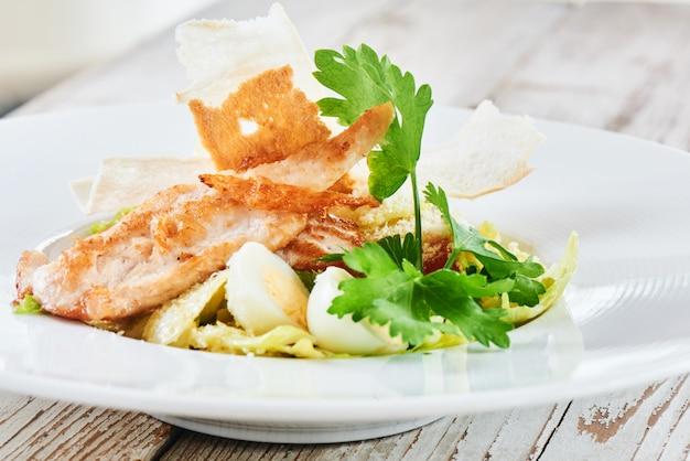 Kippensalade en gekookte eieren die op een witte plaat worden gediend