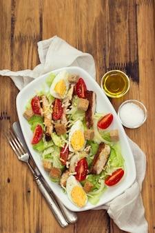 Kippensalade met gekookt ei op witte schotel